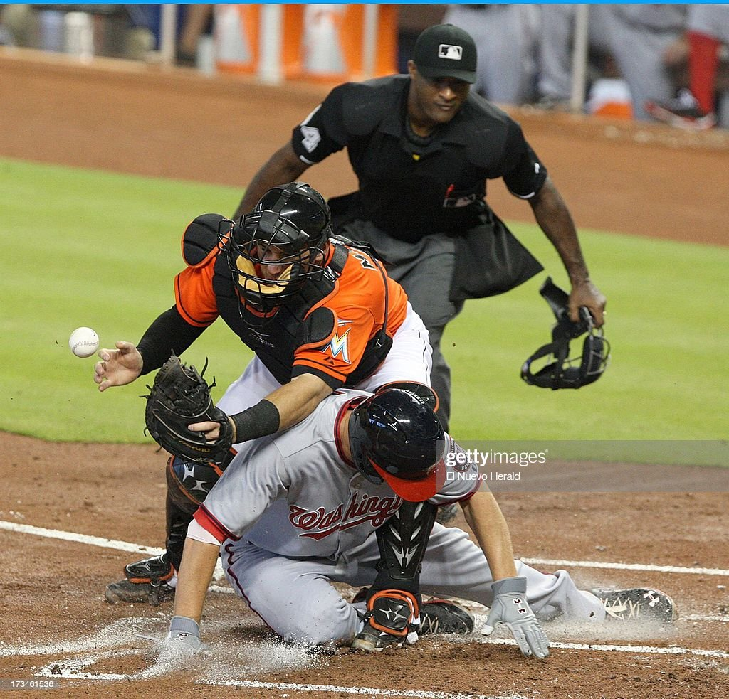 Washington Nationals' Adam LaRoche scores past Miami Marlins catcher Jeff Mathis loses the ball at home plate during the second inning at Marlins Park in Miami, Florida, Sunday, July 14, 2013.