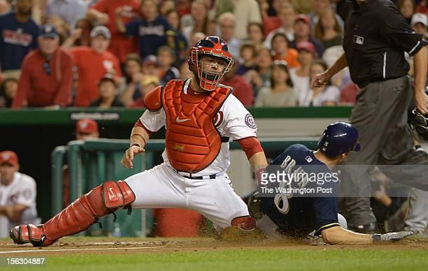 Washington Nationals catcher Jesus Flores puts the tag on Milwaukee Brewers left fielder Ryan Braun on a throw from center fielder Bryce Harper as he...