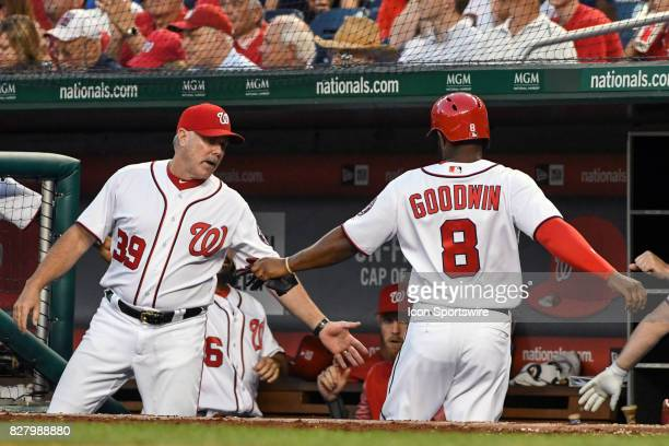 Washington Nationals center fielder Brian Goodwin is congratulated by hitting coach Rick Schu after scoring in the third inning during an MLB game...