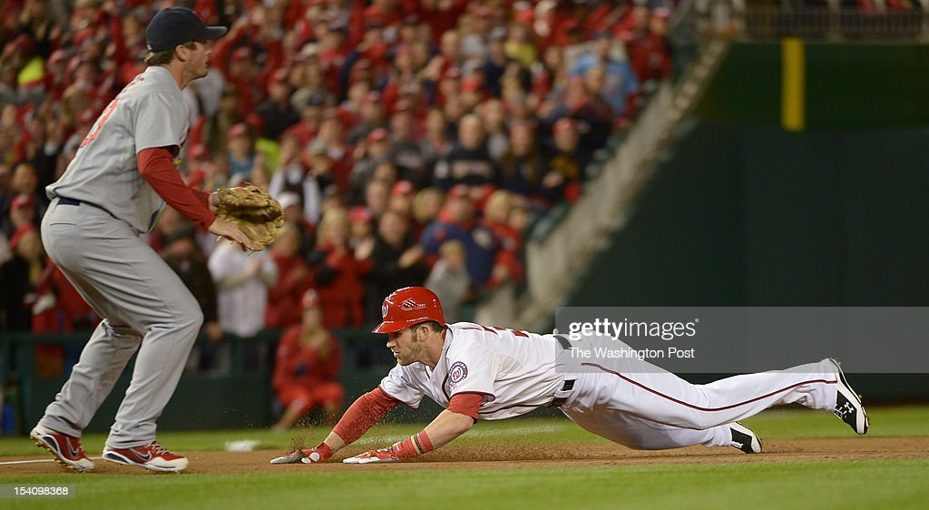 Washington Nationals center fielder Bryce Harper (34) slides into third on an RBI triple that scored Jayson Werth as St. Louis Cardinals third baseman David Freese (23) waits for the throw in the bottom of the first inning during game five of the NLDS on Oct. 12, 2012 in Washington, DC