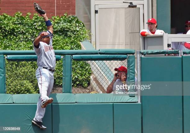 Washington Nationals center fielder Marlon Byrd robs a homerun from Philadelphia Phillies Bobby Abreu while a member of the grounds crew watches...