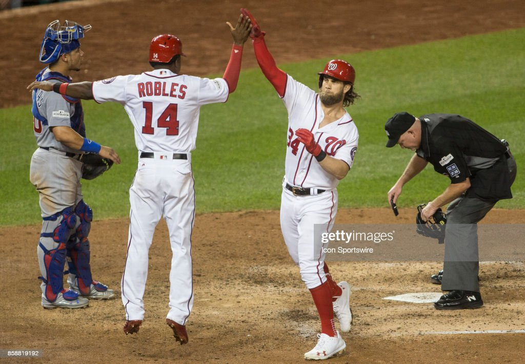 Washington Nationals center fielder Victor Robles (14) greets two run home run hitter right fielder Bryce Harper (34) at home plate during game two of the NLDS between the Chicago Cubs and the Washington Nationals on October 7, 2017, at Nationals Park, in Washington D.C. The Nationals defeated the Cubs 6-3.