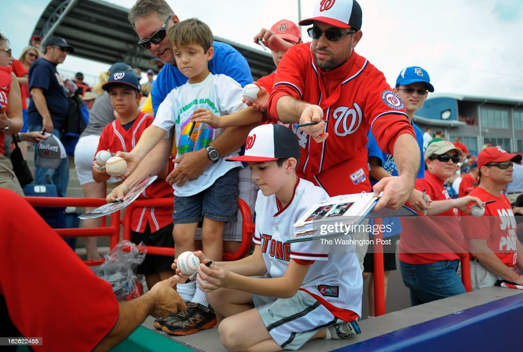 Washington Nationals fans gather around to collect autographs from players before the Florida Marlins play the Washington Nationals in Grapefruit League baseball in Viera FL, February 24, 2012 .
