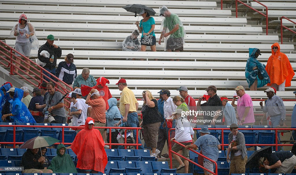 Washington Nationals fans head for cover for a mid game rain delay as the Florida Marlins tie the Washington Nationals 2 -2 in 10 innings during Grapefruit League baseball in Viera FL, February 24, 2012 .