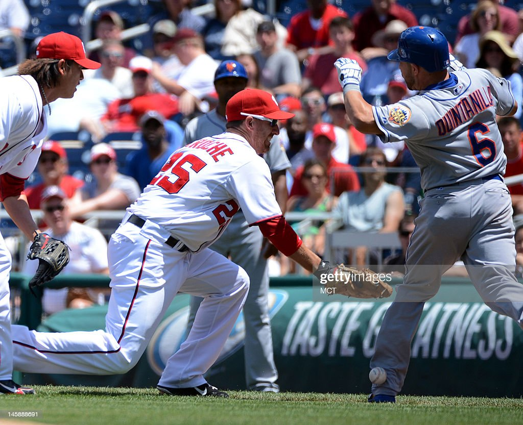 Washington Nationals first baseman Adam LaRoche misplays the ball as New York Mets shortstop Omar Quintanilla avoids a possible tag on an infield...