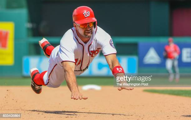 Washington Nationals first baseman Ryan Zimmerman dives for third base but is tagged out by Los Angeles Angels third baseman Luis Valbuena in the...