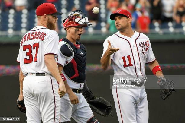 Washington Nationals first baseman Ryan Zimmerman tosses the game ball to Nationals starting pitcher Stephen Strasburg after he pitched a complete...