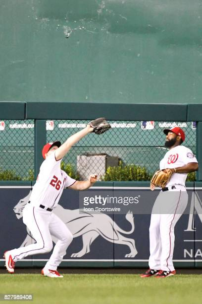 Washington Nationals left fielder Adam Lind catches a fly ball in front of center fielder Brian Goodwin during an MLB game between the Miami Marlins...