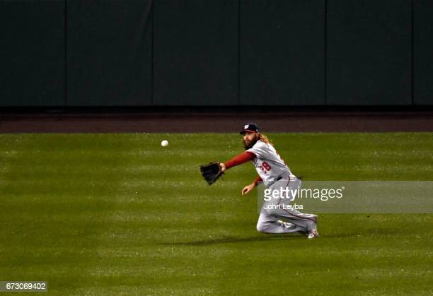 Washington Nationals left fielder Jayson Werth slides on one knee to catch a fly ball hit by Colorado Rockies left fielder Gerardo Parra during the...