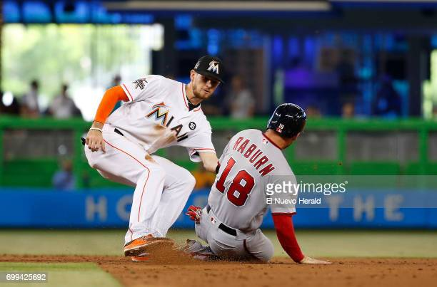 Washington Nationals left fielder Ryan Raburn slides as Miami Marlins shortstop JT Riddle tags him out during the third inning on Wednesday June 21...