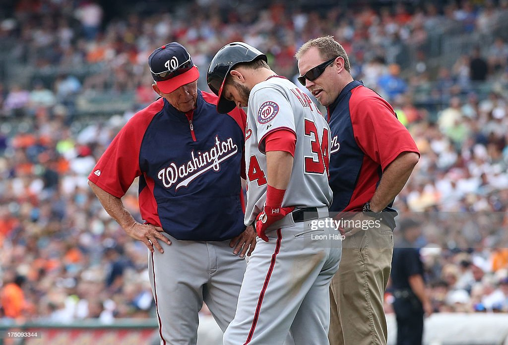 Washington Nationals manager Davey Johnson #5 and team trainer Lee Kuntz check on <a gi-track='captionPersonalityLinkClicked' href=/galleries/search?phrase=Bryce+Harper&family=editorial&specificpeople=5926486 ng-click='$event.stopPropagation()'>Bryce Harper</a> #34 during the seventh innng of the game against the Detroit Tigers at Comerica Park on July 31, 2013 in Detroit, Michigan. The Tigers defeated the Nationals 11-1.
