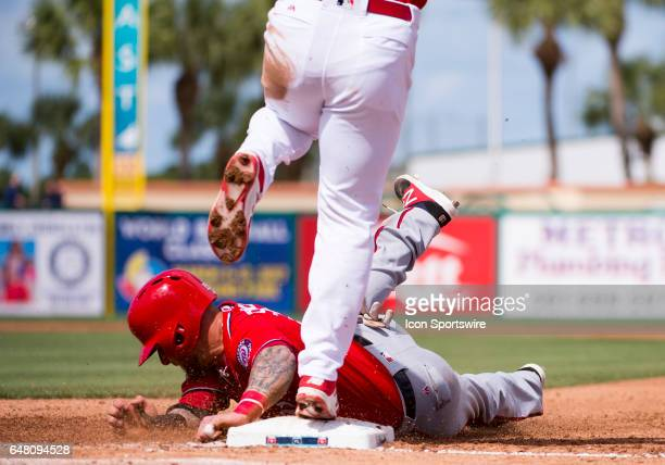 Washington Nationals NonRoster Invitee Outfielder Brandon Snyder slides back to first base with St Louis Cardinals Infielder Jedd Gyorko during an...