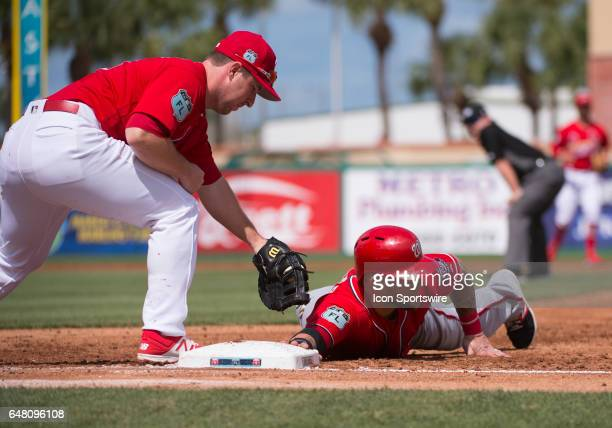 Washington Nationals NonRoster Invitee Outfielder Brandon Snyder slides back to first base as St Louis Cardinals Infielder Jedd Gyorko attempts to...