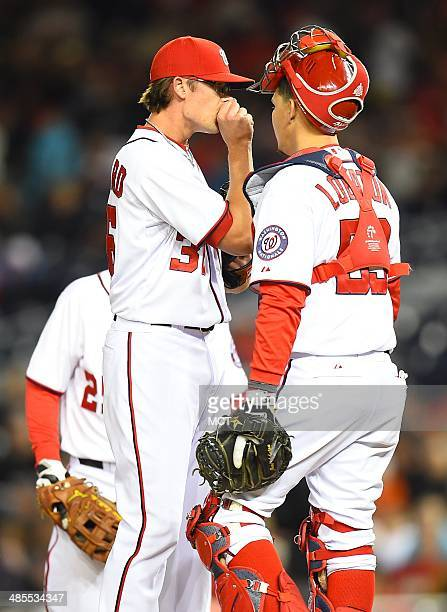 Washington Nationals relief pitcher Tyler Clippard blows into his hand to stay warm during a meeting on the mound in the eighth inning against the St...