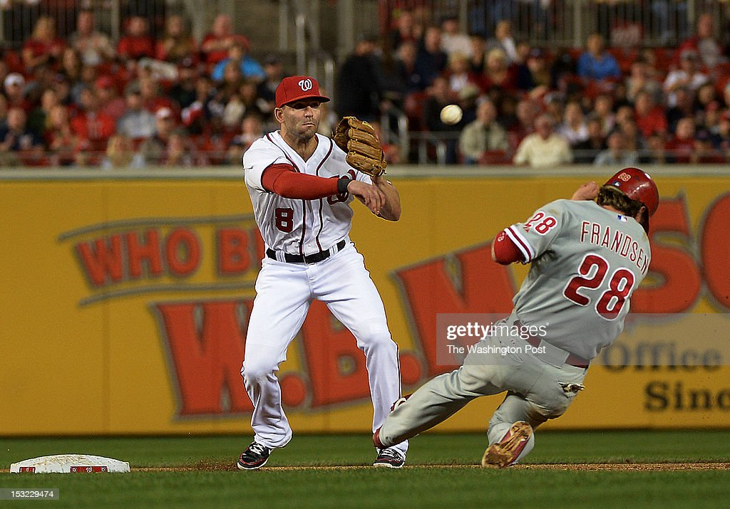 Washington Nationals second baseman Danny Espinosa (8) tags out Philadelphia Phillies third baseman Kevin Frandsen (28) as he throws the ball to turn the double play on a hit by Philadelphia Phillies left fielder John Mayberry Jr. (15) during the game at Nationals Park on Monday, October 1, 2012