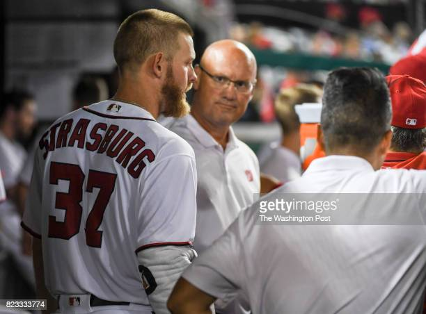 Washington Nationals starting pitcher Stephen Strasburg talks with the training staff after the seventh inning against the Chicago Cubs in Washington...