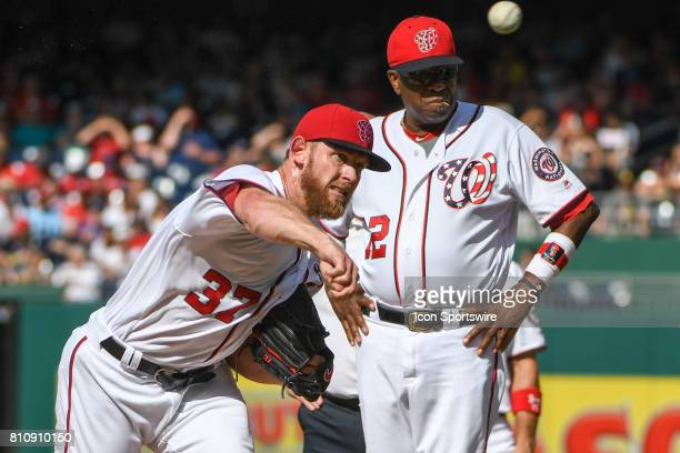 Washington Nationals starting pitcher Stephen Strasburg throws under the watchful eye of manager Dusty Baker after being hit in the hip on a...