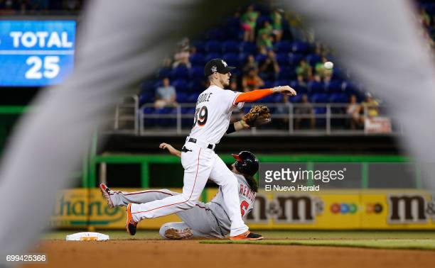 Washington Nationals third baseman Anthony Rendon slides as Miami Marlins shortstop JT Riddle throws to first base to complete a double play during...