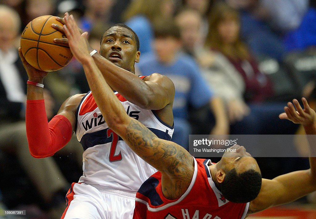 Washington point guard John Wall (2), left, draws a foul on Atlanta point guard Devin Harris (34) for a 3 point play at ther end of the 3rd quarter as the Washington Wizards play Atlanta Hawks in NBA basketball at the Verizon Center in Washington DC, January 12, 2012 .