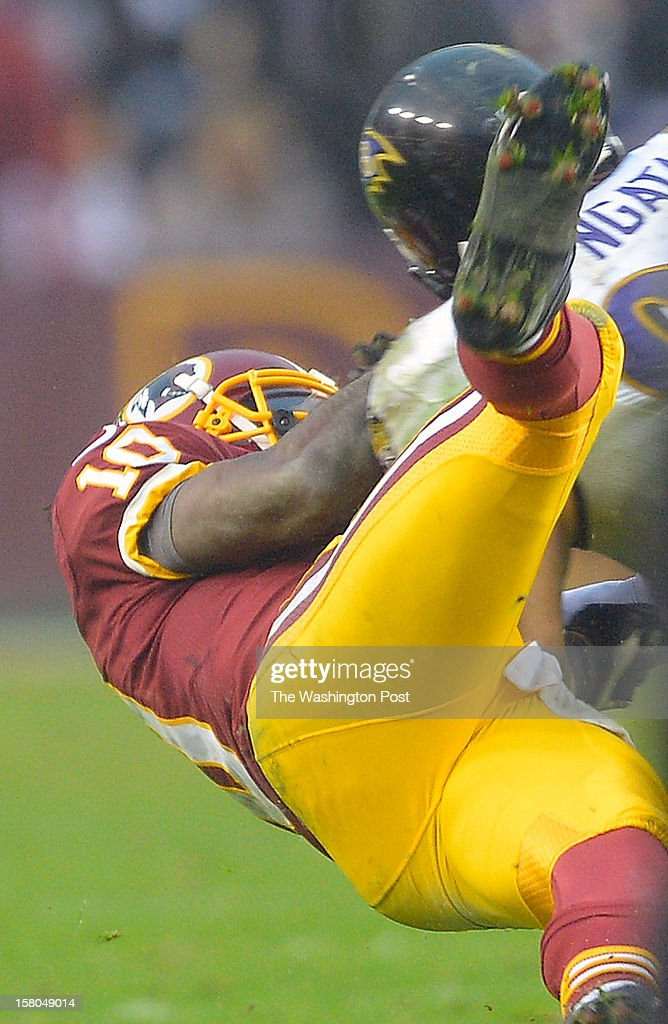Washington quarterback Robert Griffin III (10), bottom , is injured on a hit by Baltimore's defensive end Haloti Ngata (92) in the 4th quarter as the Washington Redskins defeat the Baltimore Ravens 31 - 28 at FedEx Feild in Landover MD, December 9, 2012 .