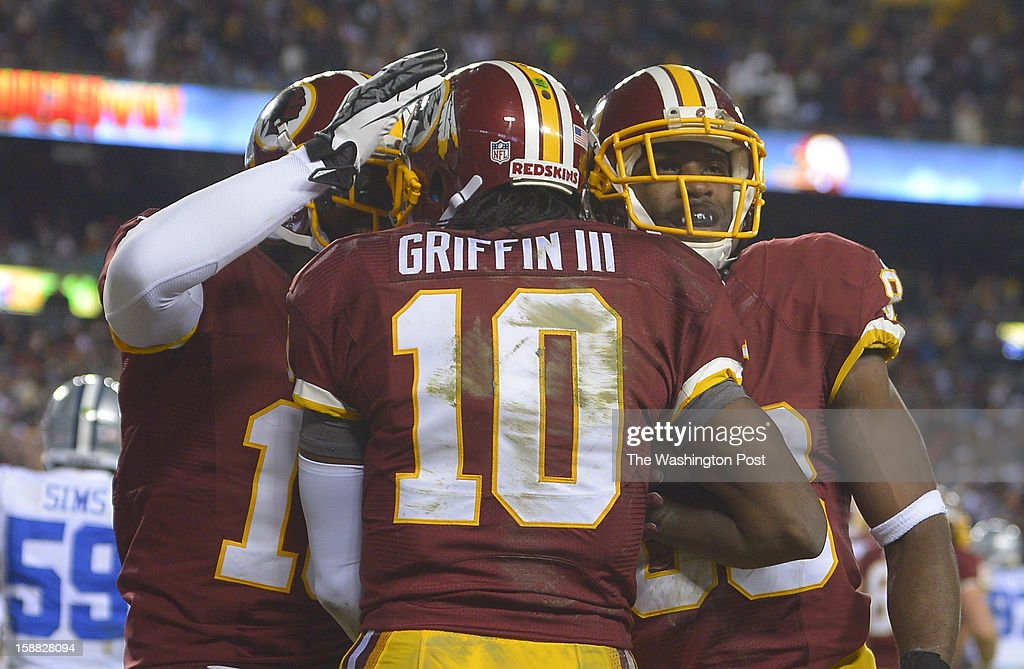 Washington quarterback Robert Griffin III (10) is congratulated by Washington wide receiver Josh Morgan (15) and Washington wide receiver Pierre Garcon (88) after Griffin scored a third quarter touchdown as the Washington Redskins play the Dallas Cowboys for first place of the NFC East division and a playoff spot at FedEx in Landover MD, December 30, 2012 .
