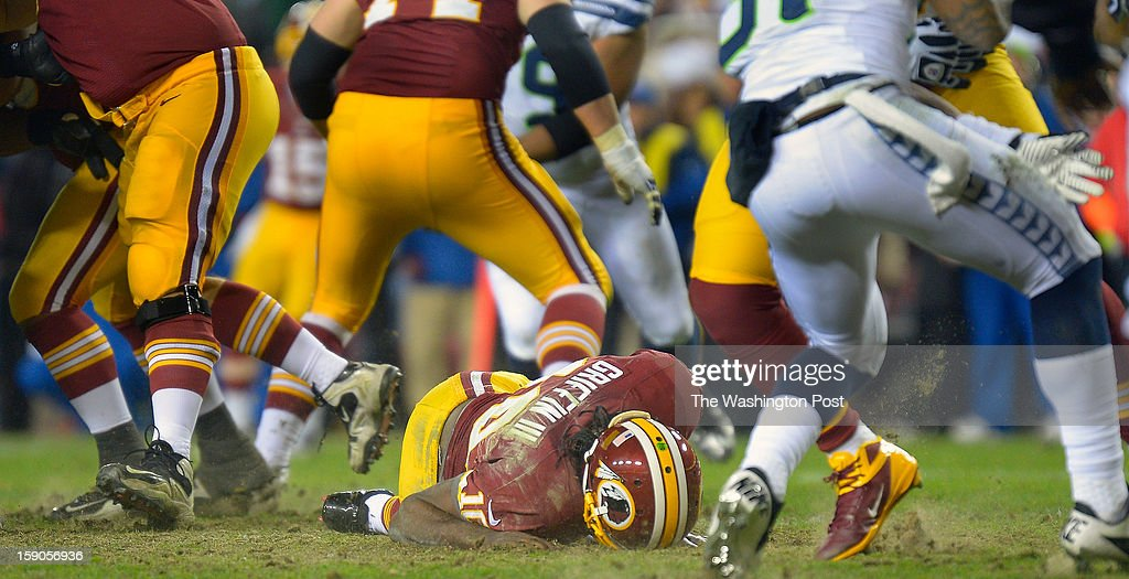 Washington quarterback Robert Griffin III (10) lies on the ground after injuring his right knee going after fumble in the 4th quarter as the Washington Redskins play the Seattle Seahawks in the first round of the NFC playoffs at FedEx Field in Landover MD, January 6, 2012 .