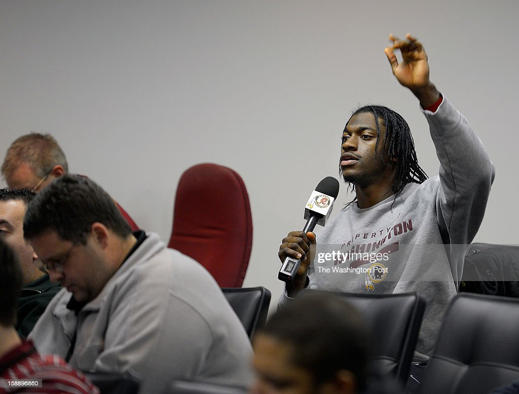 Washington quarterback Robert Griffin III sneaks into the back of the auditorium to ask a question of head coach Mike Shanahan during a press conference on the upcoming playoff game against the Seattle Seahawks. The conference was held at Redskins Park in Ashburn VA, January 2, 2012 .
