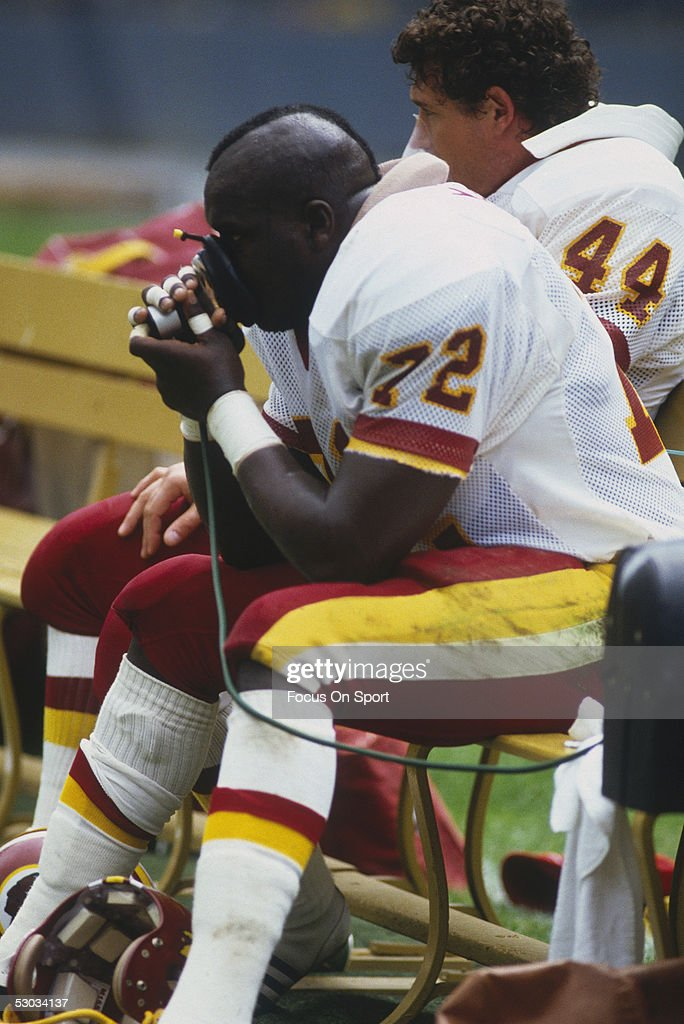 Washington Redskins' Dexter Manley sits on the sidelines with an oxygen mask during a game