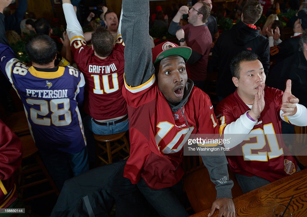 Washington Redskins fans, Jamari Dumas, center, and Minho Kong, right, watch their team take on the Dallas Cowboys at Crystal City Sports Pub on Sunday December 30, 2012 in Arlington, VA. The Redskins defeated the Cowboys to make the playoffs.