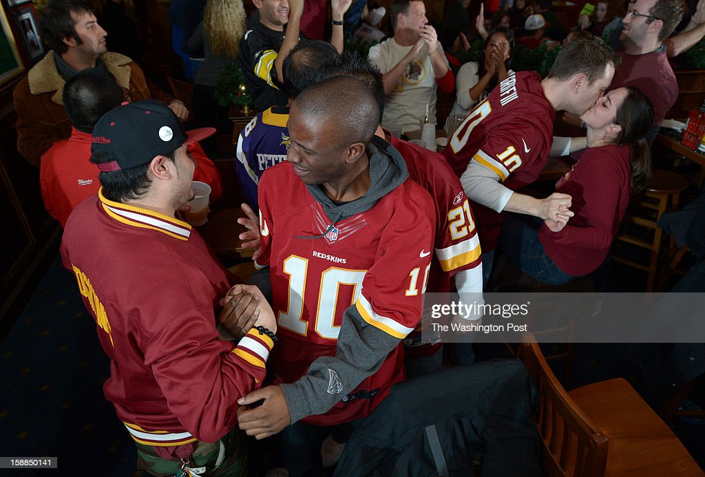 Washington Redskins fans, Peter Greiss, left, and Jamari Dumas, center, celebrate a second half score against the Dallas Cowboys at Crystal City Sports Pub on Sunday December 30, 2012 in Arlington, VA. The Redskins defeated the Cowboys to make the playoffs.