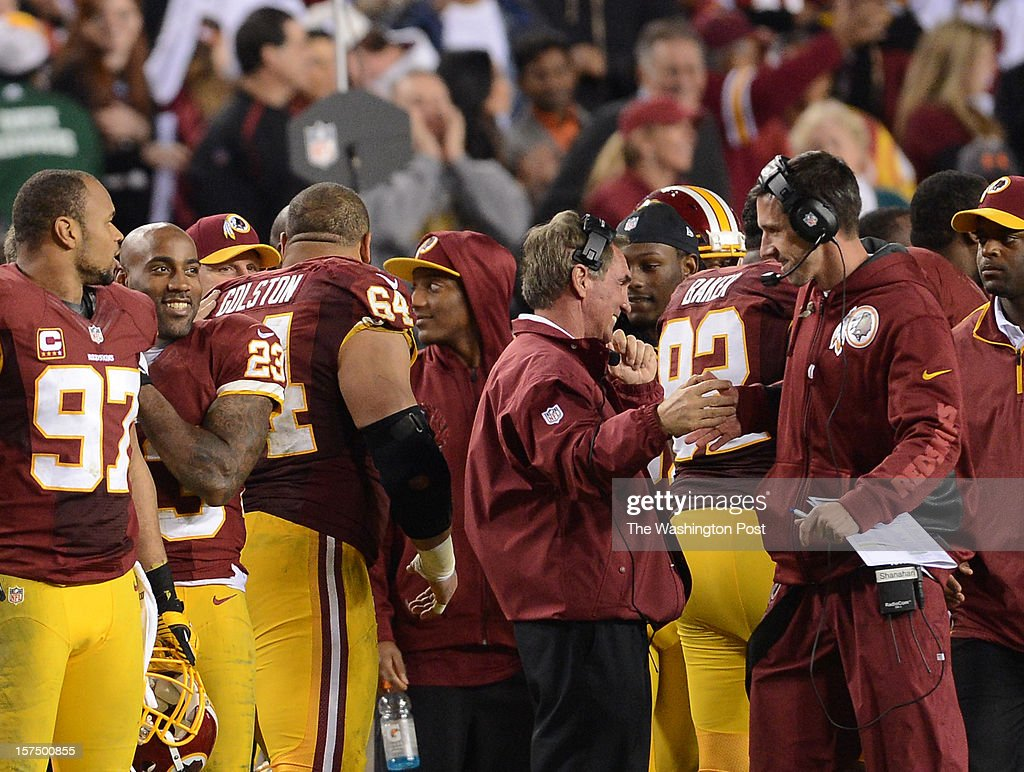 Washington Redskins head coach Mike Shanahan shakes hands with his son and offensive coordinator Kyle Shanahan after winning the game between the Washington Redskins and the New York Giants at Fed Ex Field on Monday, December 3, 2012. The Washington Redskins defeated the New York Giants 17-16.
