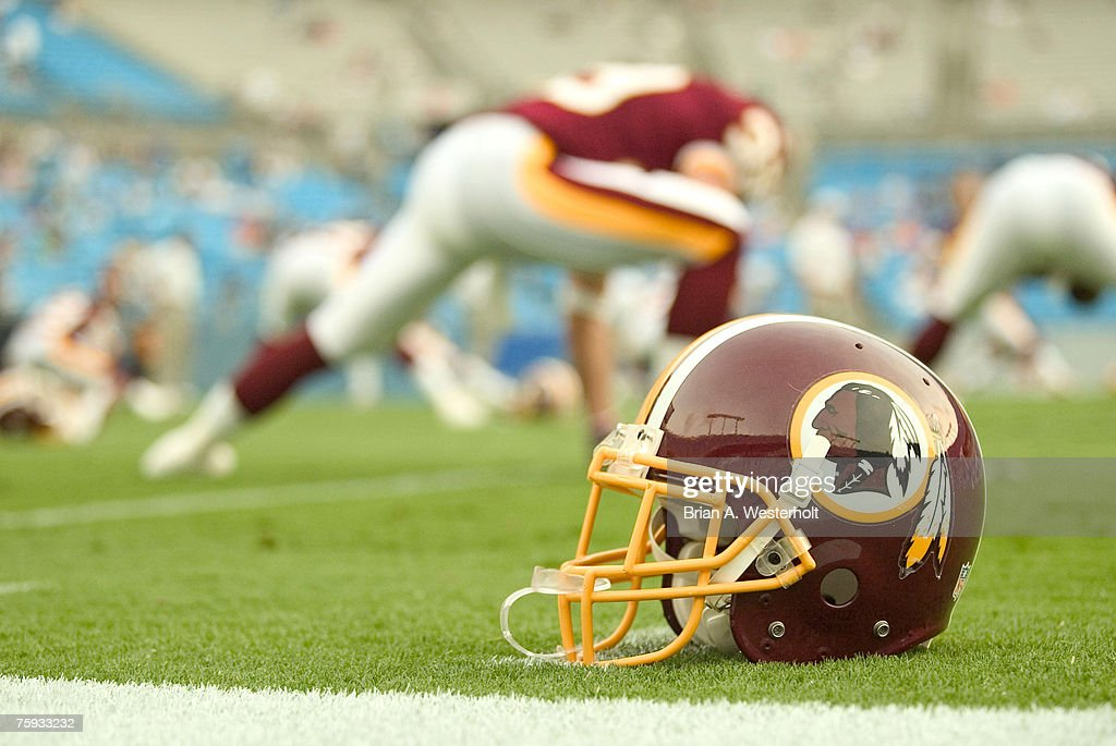A Washington Redskins helmet rests on te field as the team goes through their pregame stretching prior to playing the Carolina Panthers at Bank of...