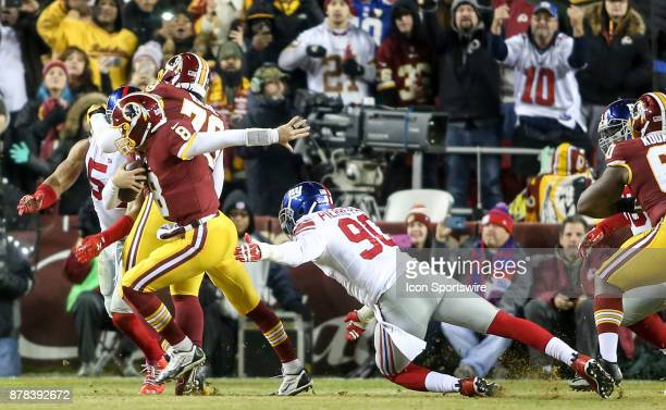 Washington Redskins quarterback Kirk Cousins sprints away from a tackle by New York Giants defensive end Jason PierrePaul during a NFL game between...