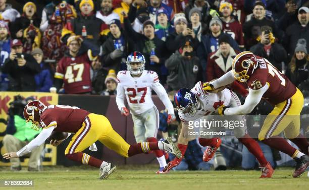 Washington Redskins quarterback Kirk Cousins stumbles after a tackle by New York Giants defensive end Olivier Vernon during a NFL game between the...