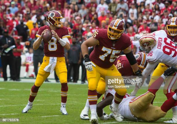 Washington Redskins quarterback Kirk Cousins surveys the field from the pocket while guard Brandon Scherff ensures his safety during a football game...