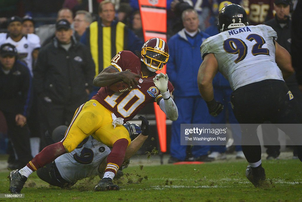 Washington Redskins quarterback Robert Griffin III (10) carries the ball before being hit by Baltimore Ravens defensive end Haloti Ngata (92) in the fourth quarter forcing Griffin out of the game during a game between the Baltimore Ravens and Washington Redskins at FedEx Field on December 9, 2012 in Landover, Md.