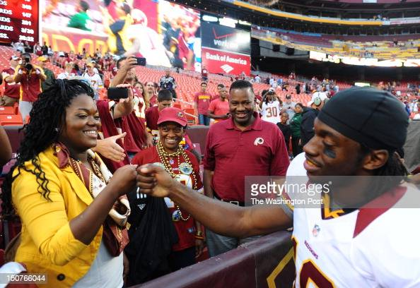 Washington Redskins quarterback Robert Griffin III fist bumbs with his sister Dejon as their parents Robert Jr and Jacqueline look on following their...