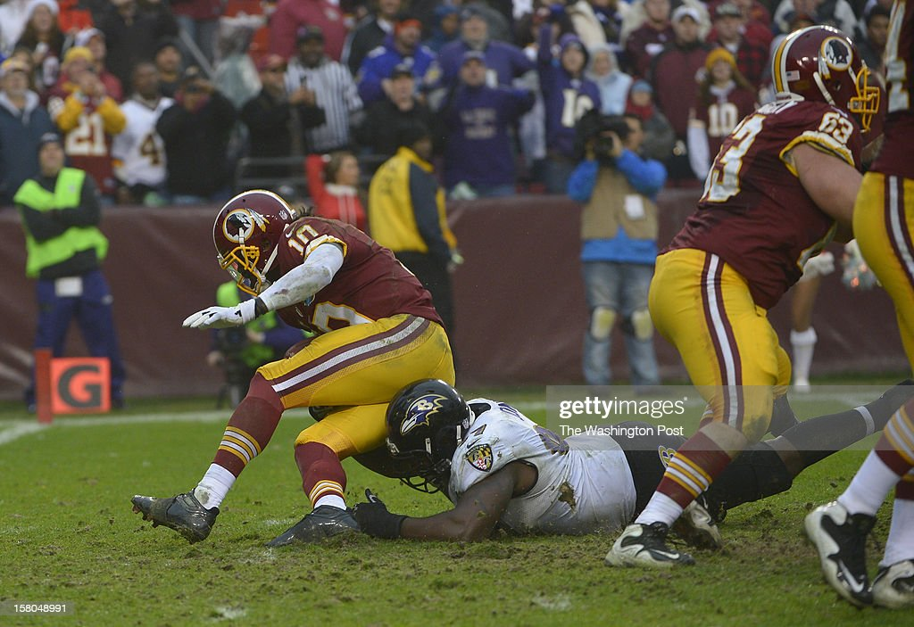 Washington Redskins quarterback Robert Griffin III (10) goes down on a run when he was hit by Baltimore Ravens defensive end Arthur Jones (97) on a play injured Griffin during a game between the Baltimore Ravens and Washington Redskins at FedEx Field on December 9, 2012 in Landover, Md.