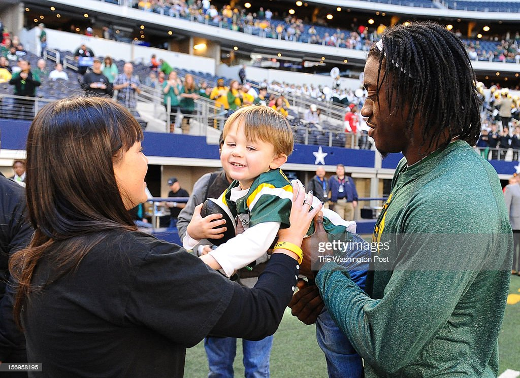Washington Redskins quarterback Robert Griffin III (10) hands over Jaytn Briles, 3, (grandson of the Baylor head coach) to his aunt Jancy Briles prior to the Baylor game against Texas Tech at Cowboys stadium on November. 24, 2012 in Arlington, TX