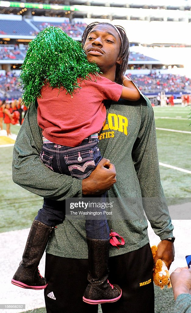 Washington Redskins quarterback Robert Griffin III (10) hugs his niece Jania Moten,4, prior to the Baylor game against Texas Tech at Cowboys stadium on November. 24, 2012 in Arlington, TX