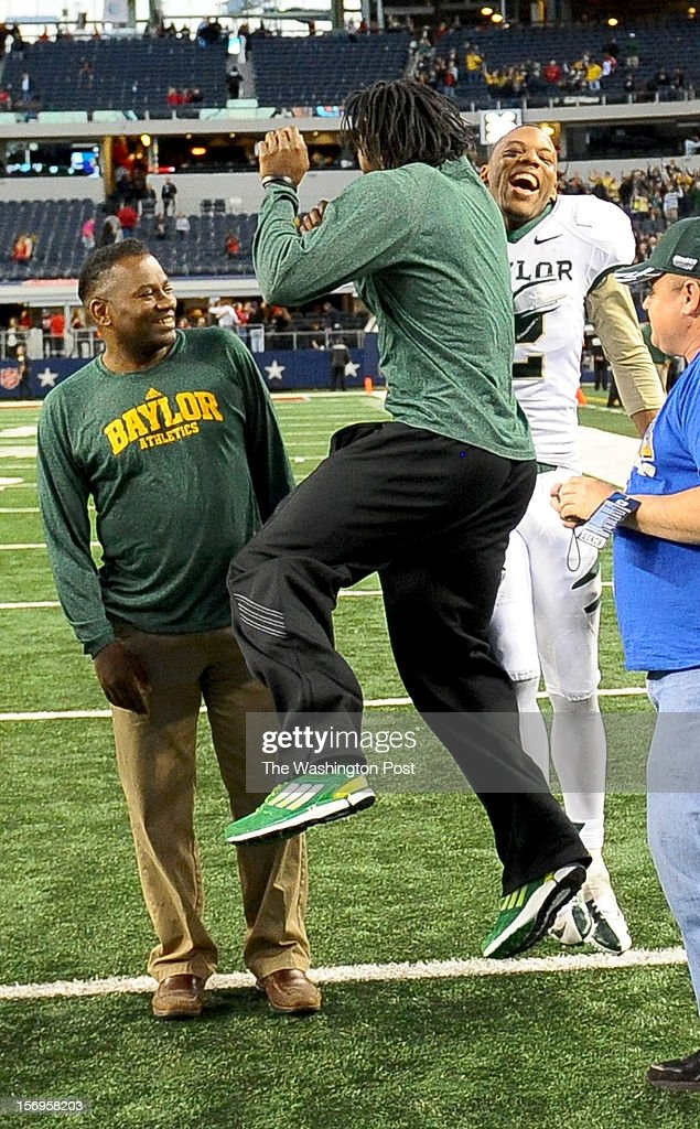 Washington Redskins quarterback Robert Griffin III (10) jumps for joy with Baylor cornerback B.J. Allen (2) as his dad Robert Griffin looks on after their overtime win against Texas Tech at Cowboys stadium on November. 24, 2012 in Arlington, TX