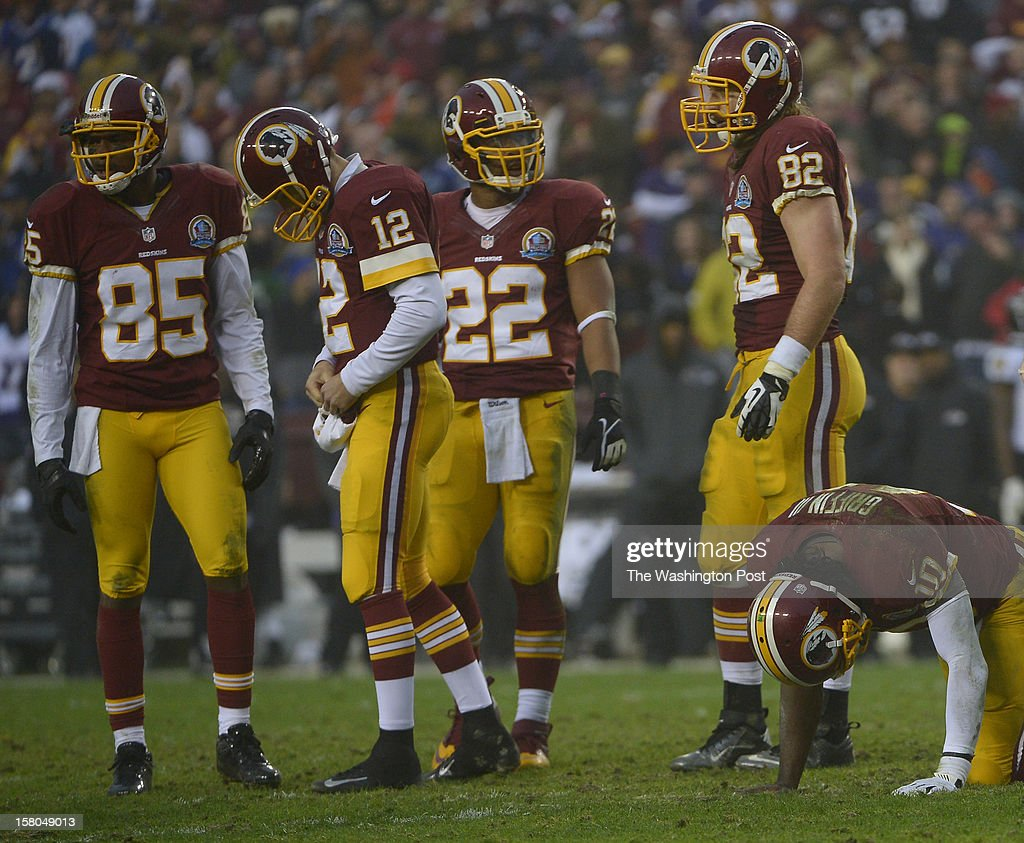 Washington Redskins quarterback Robert Griffin III (10) right, kneels down before being helped off the field for good in the fourth quarter during a game between the Baltimore Ravens and Washington Redskins at FedEx Field on December 9, 2012 in Landover, Md. At center is Washington Redskins quarterback Kirk Cousins (12) who backed up Griffin and led the team past Baltimore 31-28 in overtime.
