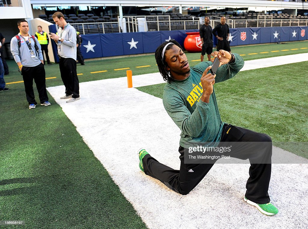 Washington Redskins quarterback Robert Griffin III (10) snaps a picture with a phone for friends prior to the Baylor game against Texas Tech at Cowboys stadium on November. 24, 2012 in Arlington, TX