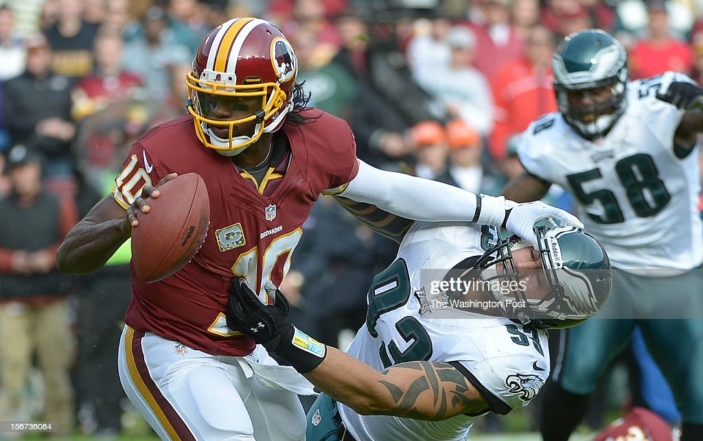 Washington Redskins quarterback Robert Griffin III (10) stiff arms Philadelphia Eagles defensive end Jason Babin (93) as he pitches out during 2nd quarter action at FedEx field on November. 18, 2012 in Landover, MD