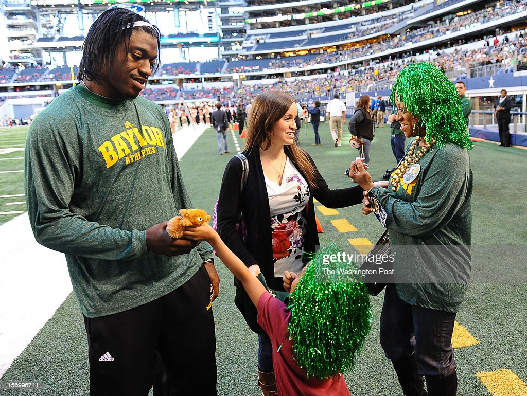 Washington Redskins quarterback Robert Griffin III (10) talks with his niece Jania Moten,4, as his fiance Rebecca Liddicoat talks with RGIII's mother Jacqueline Griffin prior to the Baylor game against Texas Tech at Cowboys stadium on November. 24, 2012 in Arlington, TX