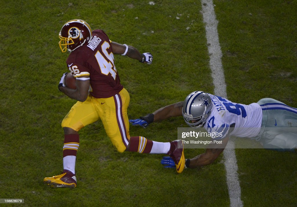 Washington Redskins running back Alfred Morris (46) carries the ball for a first down as Dallas Cowboys defensive end Jason Hatcher (97) tries to tackle him in the second quarter during a game between the Dallas Cowboys and Washington Redskins at FedEx Field on December 30, 2012 in Landover, Md.