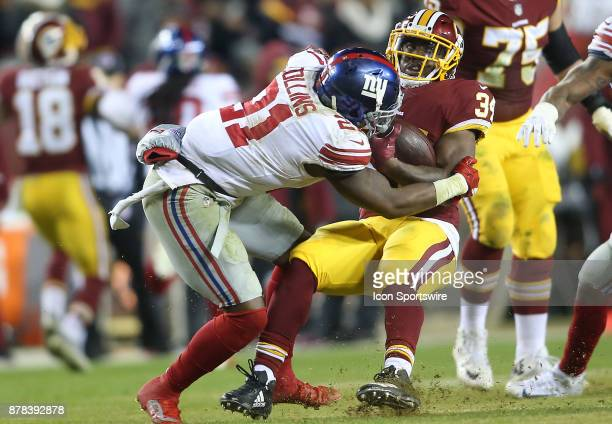 Washington Redskins running back Byron Marshall held up by New York Giants strong safety Landon Collins during a NFL game between the Washington...