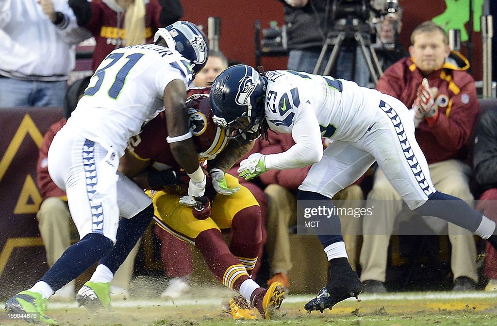 Washington Redskins running back Evan Royster (22) scores on a touchdown catch between Seattle Seahawks strong safety Kam Chancellor (31) and Seahawks free safety Earl Thomas (29) in the first quarter of an NFC wild-card playoff game at FedEx Field in Landover, Maryland, Sunday, January 6, 2013.