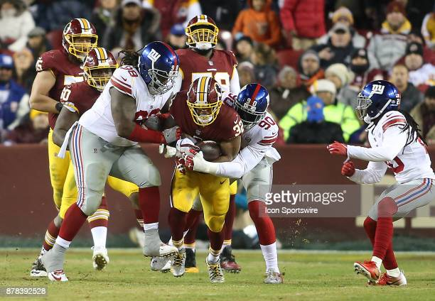 Washington Redskins running back Samaje Perine is trapped by New York Giants defensive tackle Damon Harrison and defensive end Jason PierrePaul...