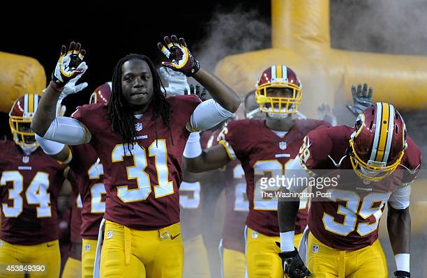 Washington Redskins strong safety Brandon Meriweather and along with other teammates enter the field at FedEx Field with their arms raised in the...